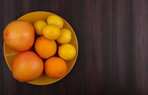 木の背景に黄色いボウルにオレンジとグレープフルーツとトップビューコピースペースレモン