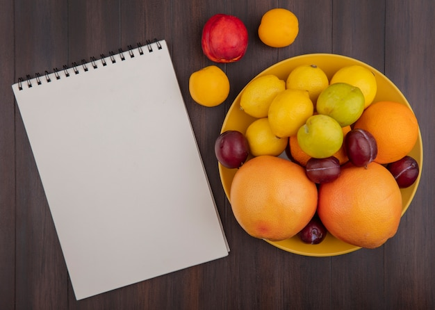 Top view  copy space lemons with oranges  plums and grapefruit in a yellow bowl with apricots and a peach with a notepad on a wooden background