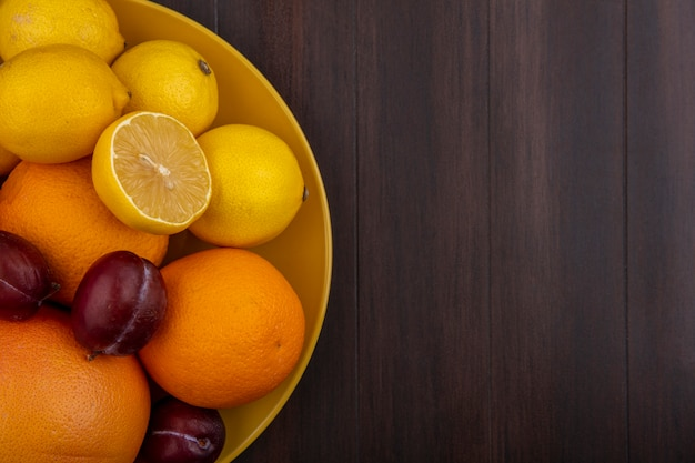 Top view  copy space lemons with oranges  plums and grapefruit in a yellow bowl on a wooden background