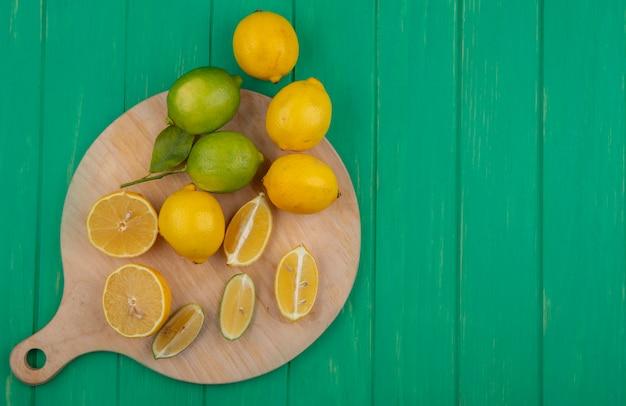 緑の背景のまな板にレモンとレモンの上面コピースペースライムスライス