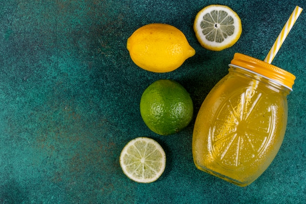 Top view copy space lime with lemonnd orange juice on green