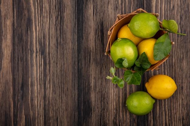 Vista dall'alto lo spazio della copia limette con limoni in un cesto su sfondo di legno