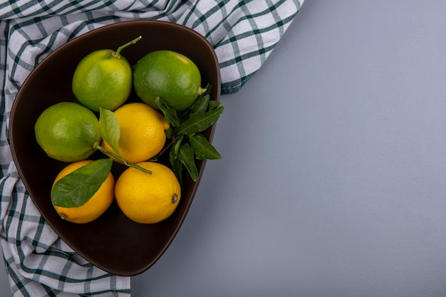 Top view  copy space limes with lemons in a bowl on a checkered towel  on a gray background