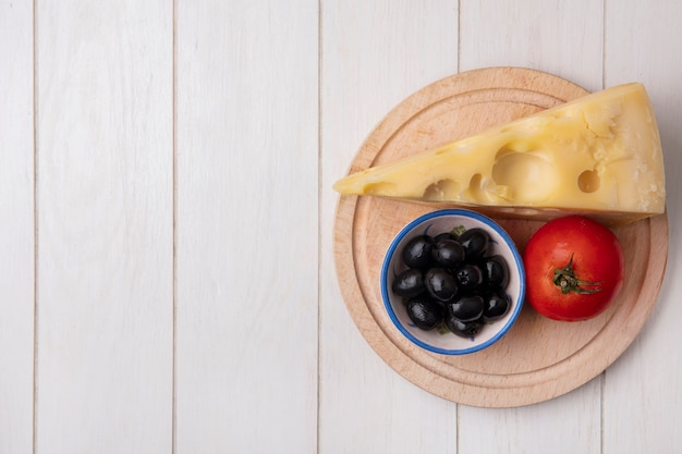 Top view  copy space maasdam cheese with olives and tomato on stand  on white background