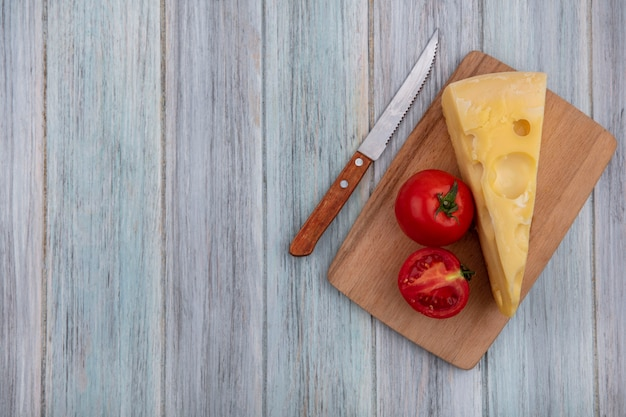 Top view  copy space maasdam cheese with tomatoes on a stand  with a knife  on a gray background