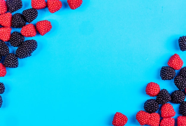 Top view copy space marmalade in the form of raspberries and blackberries on a blue background