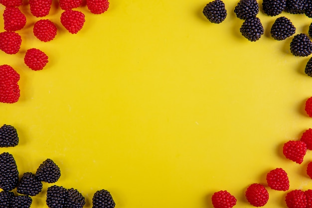 Top view copy space marmalade in the form of raspberries and blackberries on a yellow background