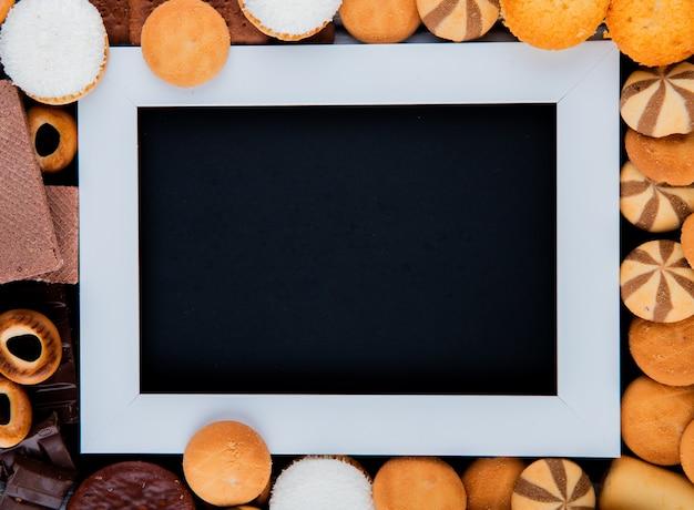 トップビューコピースペースミックスマシュマロとクッキーと黒い背景の白いフレーム