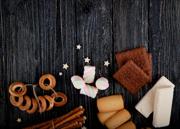 Top view copy space mix of cookies with waffles marshmallows and bread sticks on a black wooden background