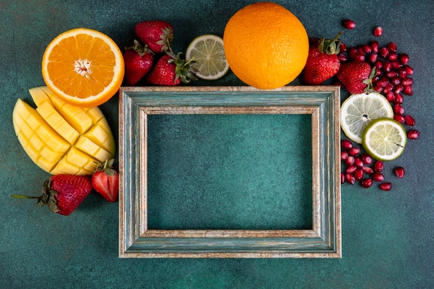 Top view  copy space mix of fruits mango  banana  strawberries  lemon  orange with frame on a green background