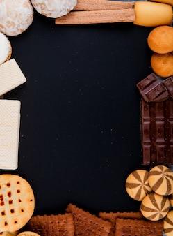 黒い背景にチョコレートとワッフルとクッキーのトップビューコピースペースミックス