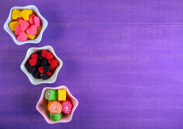 Top view copy space multi-colored marmalade in different forms in saucers for jam on a purple background