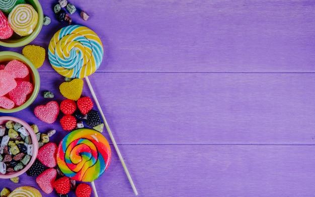 トップビューコピースペースマルチカラーマーマレードとチョコレートの石と紫色の背景にジャムの受け皿の色のつらら
