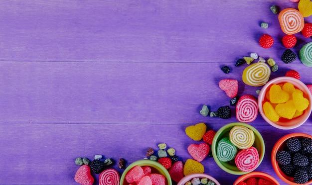 Вид сверху копией пространства разноцветного мармелада с шоколадными камнями в блюдца для варенья на фиолетовом фоне