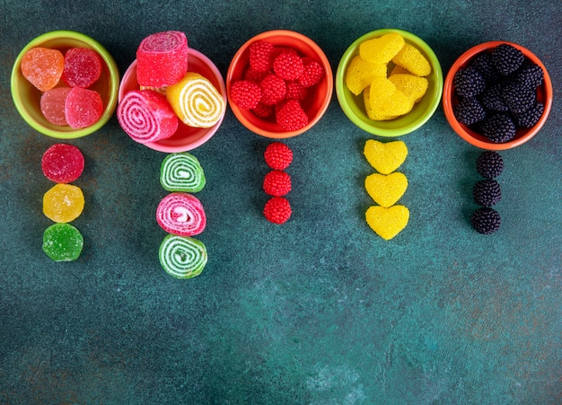 Вид сверху копией пространства разноцветных мармеладов в разноцветных тарелках для варенья на темно-зеленом фоне