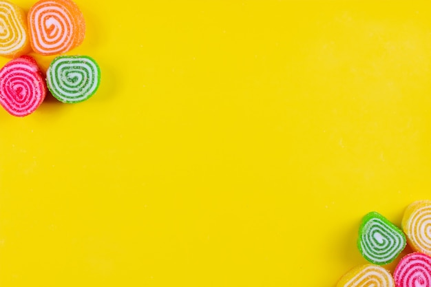 Вид сверху скопировать космический разноцветный мармелад на желтом фоне