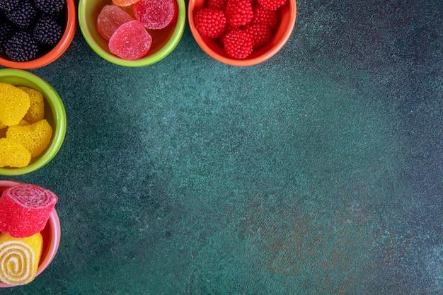 Vista dall'alto copia spazio marmellate colorate in piattini per marmellata su uno sfondo verde scuro