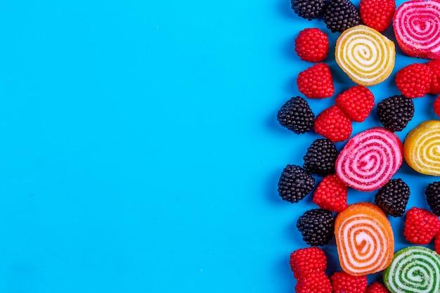 Vista dall'alto copia spazio marmellate colorate con marmellate a forma di lamponi e more su sfondo blu