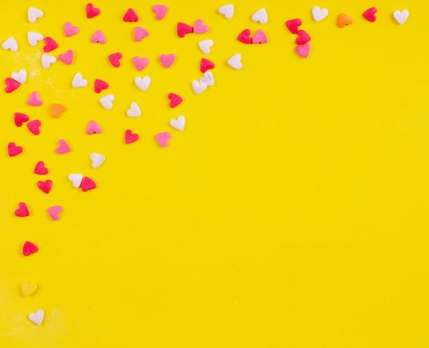 Вид сверху копией пространства разноцветных конфет в форме сердца на желтом фоне