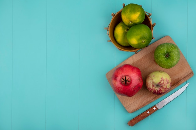 青い壁のバスケットにザクロとみかんが入ったまな板の上面コピースペース色とりどりのリンゴ