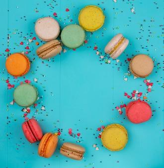 Вид сверху копировать пространство разноцветные macarons на синем фоне