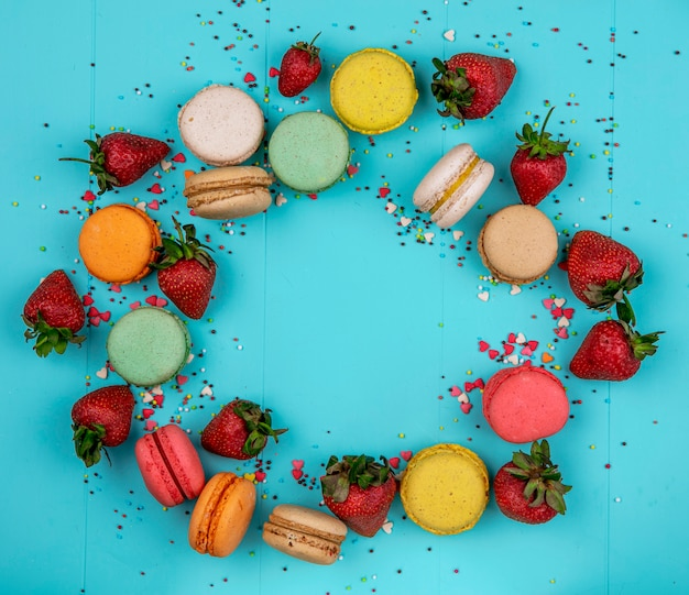 Top view copy space multicolored macarons with strawberries on a blue background