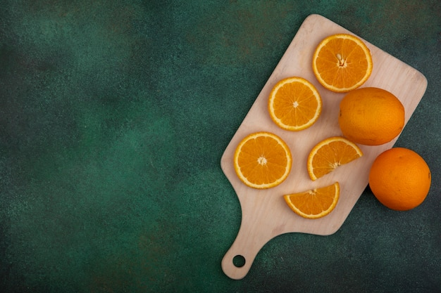 Vista dall'alto copia spazio fette d'arancia sul tagliere su sfondo verde