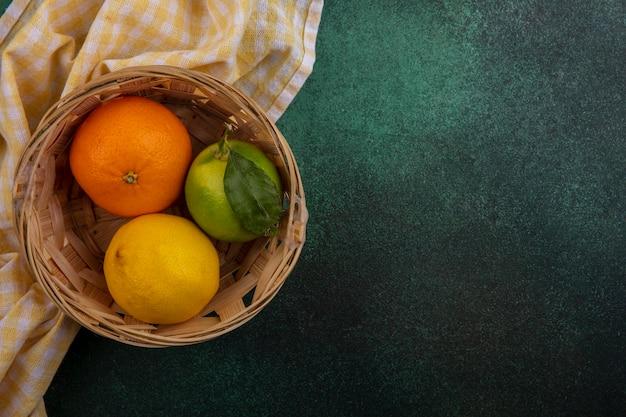 上面図コピースペースオレンジ、レモン、ライム、バスケット、緑の背景に黄色の市松模様のタオル
