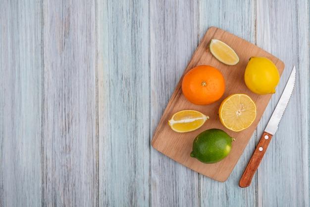 Vista dall'alto spazio copia arancione con limone e lime sul tagliere con coltello su sfondo grigio