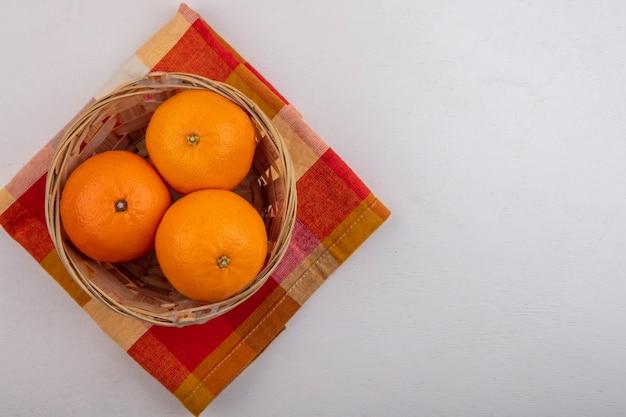 Vista dall'alto copia spazio arance nel carrello sul tovagliolo a scacchi su sfondo bianco
