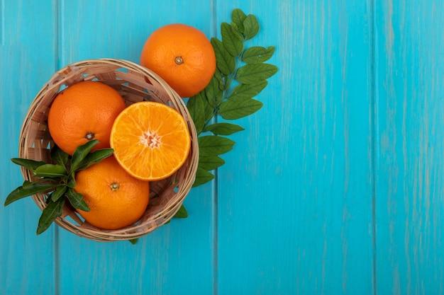 Vista dall'alto copia spazio arance in un cesto con un rametto di foglie su uno sfondo turchese