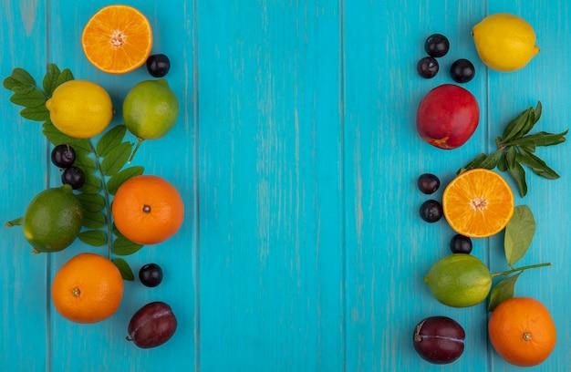 Vista dall'alto copia spazio arance con prugne ciliegia limoni limette e prugne su uno sfondo turchese