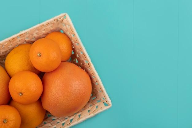 Vista dall'alto copia spazio arance con la merce nel cestino del pompelmo su sfondo turchese