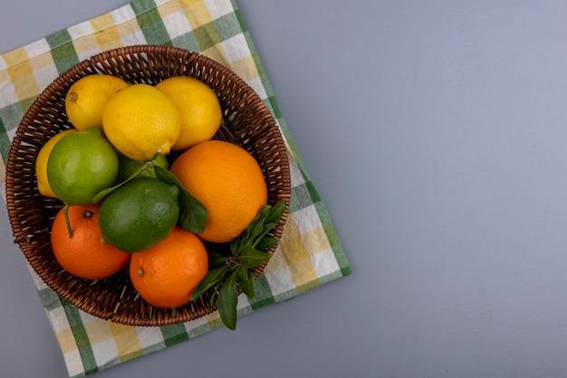 Vista dall'alto copia spazio arance con limoni e limette in un cesto su un asciugamano a scacchi giallo su sfondo grigio