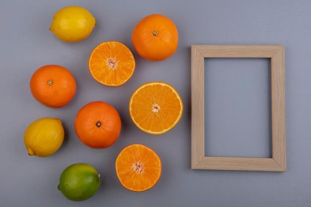 Vista dall'alto copia spazio arance con limoni limette e cornice beige su sfondo grigio