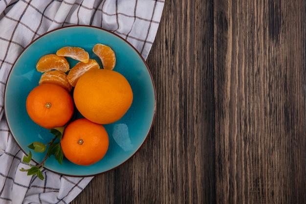 Vista dall'alto copia spazio arance con spicchi pelati su un piatto blu su un asciugamano a scacchi su uno sfondo di legno