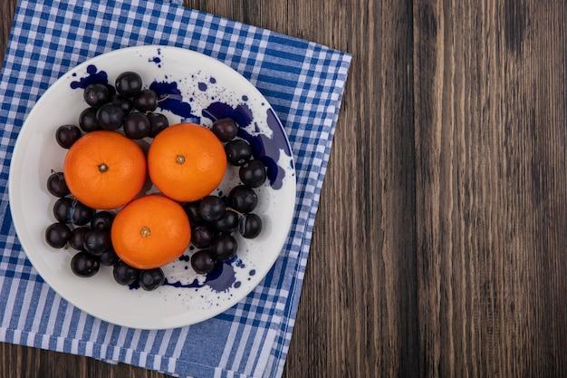 Vista dall'alto copia spazio arance con prugne sul piatto bianco con asciugamano a scacchi blu su fondo in legno