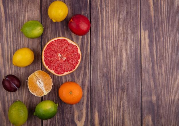 木の背景にレモンライムオレンジとハーフグレープフルーツと上面コピースペースピーチ