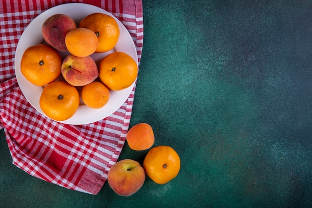Вид сверху копией пространства персики с мандаринами и абрикосами на тарелку на кухонное полотенце на зеленый