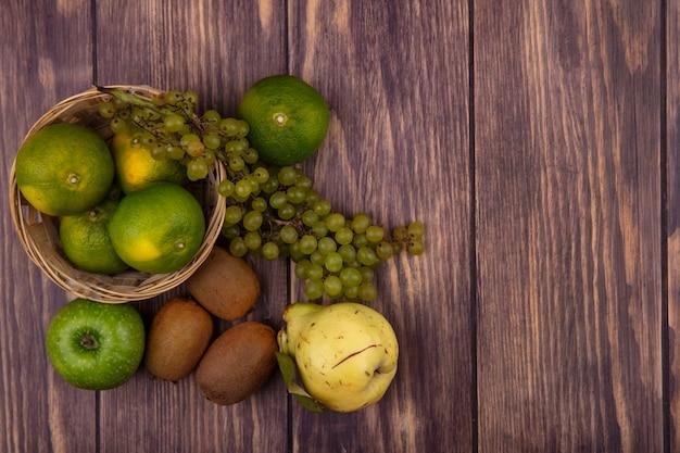 木製の壁のバスケットにキウイみかんのリンゴとブドウと上面のコピースペース梨