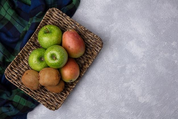 Вид сверху копией космических груш с зелеными яблоками и киви на подставке с клетчатыми полотенцами на белом фоне