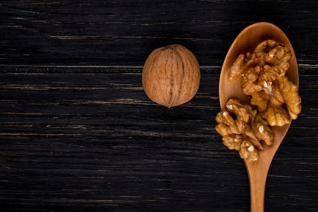 Вид сверху копия пространства очищенные грецкие орехи в деревянной ложкой и в скорлупе на черном фоне дерева