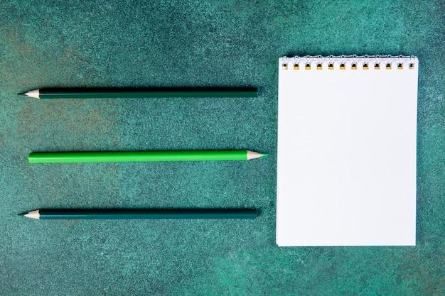 Tinta verde delle matite dello spazio della copia di vista superiore con un taccuino su un fondo verde