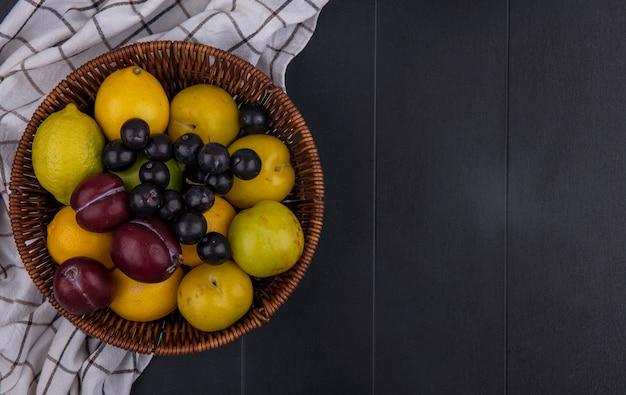 Вид сверху копия космической сливы с алычей и лимонов с лаймом в корзине на клетчатом полотенце на черном фоне