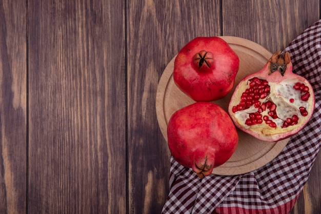 Top view copy space pomegranates on a stand on a red checkered towel on a wooden wall