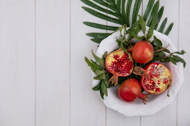 Top view  copy space pomegranates with branches leaves in a white plate on a white background