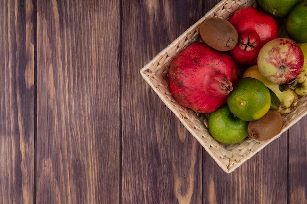 Top view copia spazio melograni con mandarini mele pere e kiwi in un cesto sulla parete in legno