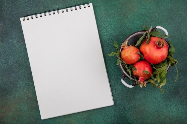 Top view copy space melograni con ramoscelli in una casseruola con un blocco note bianco su sfondo verde