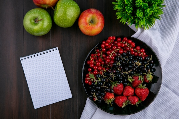 Top view copy space red and black currants with strawberries on a plate with apples and a notebook on a wooden background