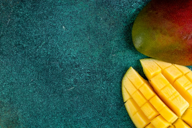 Top view copy space sliced mango on green